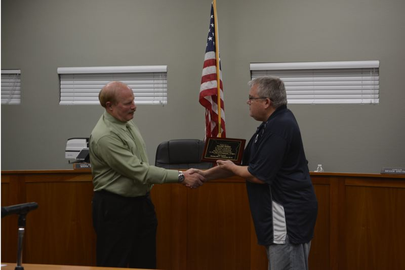 SPOTLIGHT PHOTO: COURTNEY VAUGHN - Mark Reed (left) receives a plaque recognizing him for serving eight yeras as a Scappoose city councilor Monday night, Dec. 3. To the right, Scappoose Mayor Scott Burge presents the plaque.