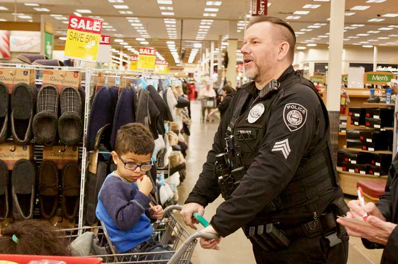 OUTLOOK PHOTO: CHRISTOPHER KEIZUR - Gresham Police Sgt. Scott Hogan gives Kevin a ride in the cart during the annual Shop with a Cop event Saturday morning, Dec. 1.