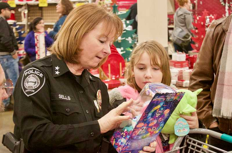 OUTLOOK PHOTO: CHRISTOPHER KEIZUR - Police Chief Robin Sells checked out some of the amazing toys one child had picked out during Shop with a Cop.