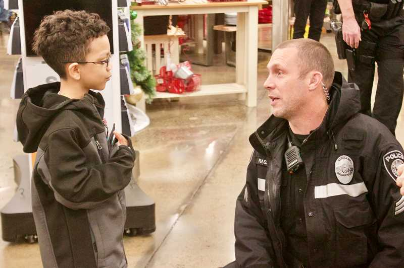 OUTLOOK PHOTO: CHRISTOPHER KEIZUR - Sgt. John Rasmussen chats with fourth-grader Nacari during Shop with a Cop.