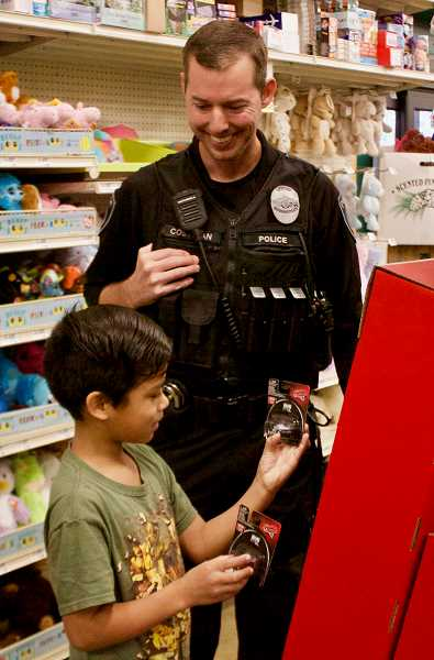 OUTLOOK PHOTO: CHRISTOPHER KEIZUR - Officer Ben Costigan helps pick out toys during the shopping spree.