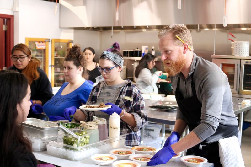 TRIBUNE PHOTO: ZANE SPARLING - Joe Williams, a culinary and math teacher, helps students serve up tacos and chicken pozole during a presentation about the new additions at Helensview School on Friday, Dec. 7.