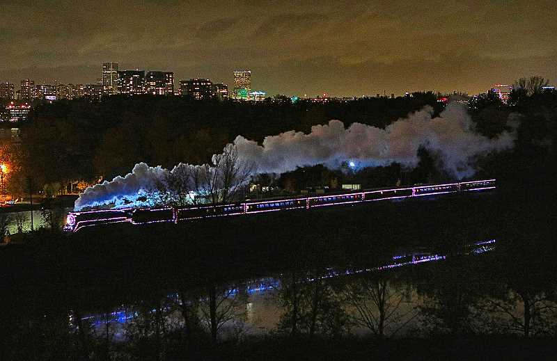DAVID F. ASHTON - Another ride on the Holiday Express comes to an end, as the antique steam train approaches Oaks Park Station after dark, its Holiday lights reflected in Oaks Bottom Lagoon below it, and the lights of Downtown Portland shining from across the Willamette River beyond it.