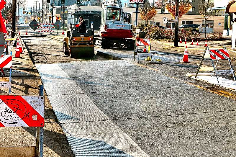 DAVID F. ASHTON - The freshly-poured concrete bus pad steams in the morning sun, as workers prepare to repave another section of the block with new asphalt.