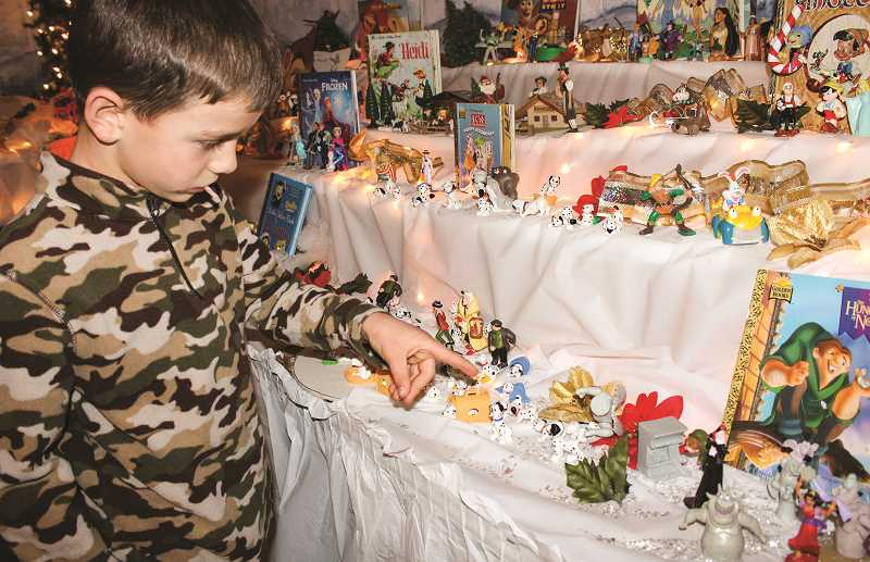 HOLLY SCHOLZ/CENTRAL OREGONIAN  - Seven-year-old Luke Holland counts the dalmatians in the storybook section of the display. Grimes has hidden 101 dalmatians throughout the scene and encourages visitors to search for them. There are also two Waldo characters hiding in the scenes.