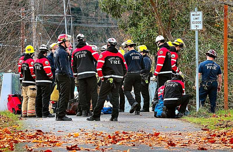 DAVID F. ASHTON - After helping the victim, who had landed in Johnson Creek, back up to the Springwater Corridor Trail after a tumble, firefighter paramedics then examined the patient. There appeared to be no injuries.