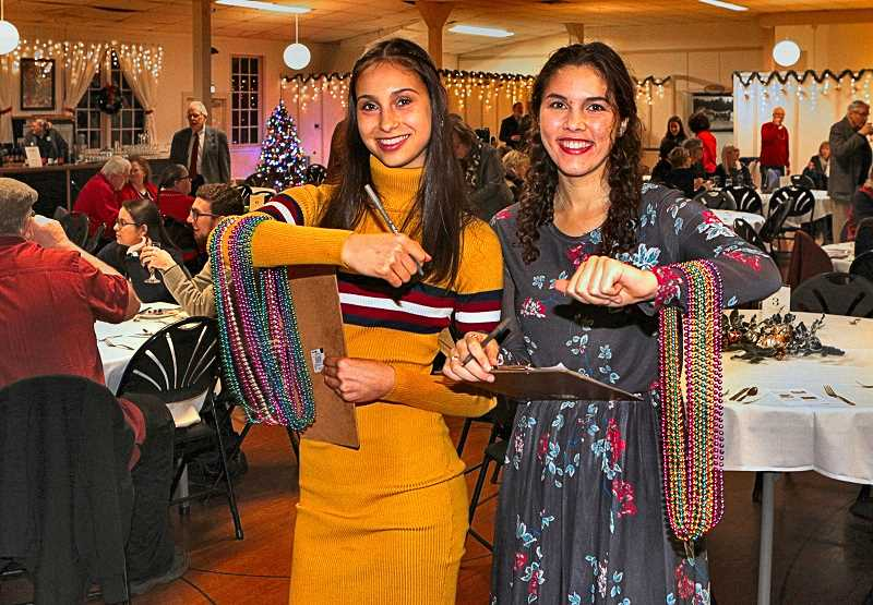 DAVID F. ASHTON - The Southeast Portland Rotary Clubs current inbound exchange student from Argentina, Agustina Sesto, left, offers Heads or Tails game beads along with her local host sister, Natalie Marcum. Agustina is enrolled at Cleveland High this year.