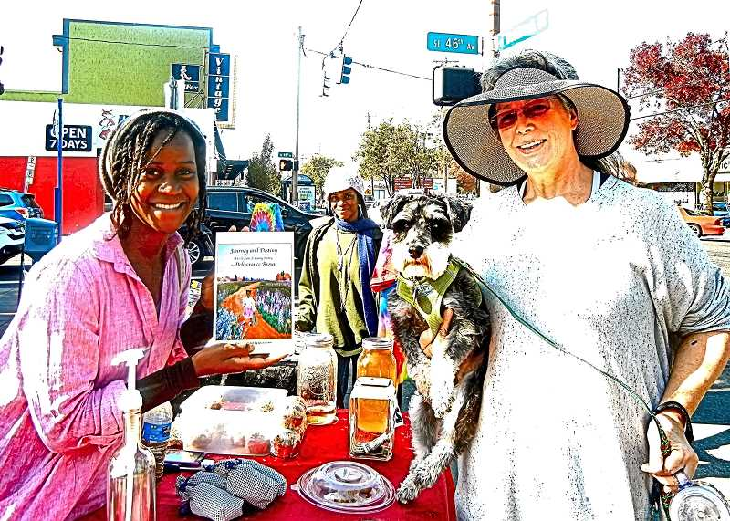 ELIZAABETH USSHER GROFF - On a recent October Sunday at the Woodstock Farmers Market, Deliverance Brown (left) held up a copy of her poetry book - which she had just sold to Woodstock resident Karen Roberti, shown holding her dog Winston.  In the background, Browns sister Andrea was selling T-shirts designed and screened by their father, Roosevelt Brown.
