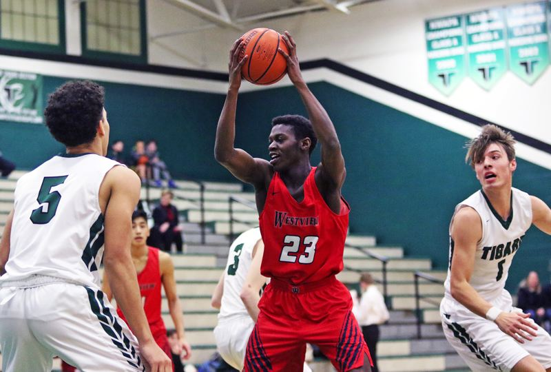 TIMES PHOTO: DAN BROOD - Westview senior Juwon Esuk grabs the ball during the Wildcats' game at Tigard on Friday.