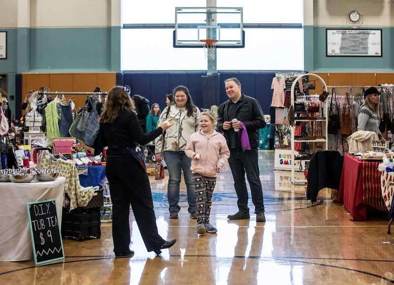 SPOKESMAN PHOTO: JONATHAN HOUSE - Ryan Dempsey, his wife Connie, and their daughter Leah enjoy checking out the booths at the Wilsonville High Holiday Bazaar.