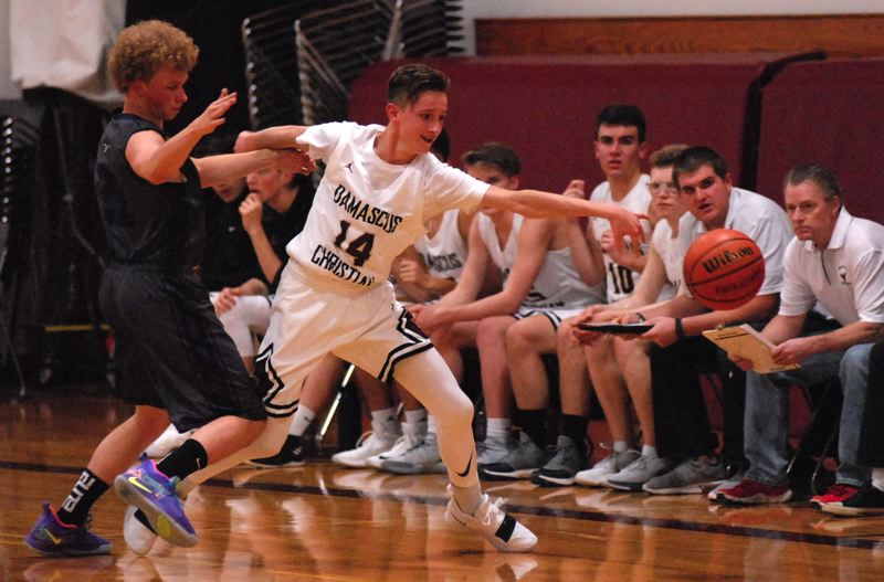 OUTLOOK PHOTO: DAVID BALL - Damascus Christians Jacob Zakharyuk reaches to complete a steal along the sideline during the Eagles' 57-53 overtime win over Central Christian on Monday.