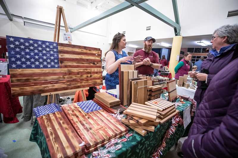 SPOKESMAN PHOTO: JONATHAN HOUSE - Lisa and David Hooley of Hooley's Woodworks chat with customers during the Holiday Market at Inza R. Wood Middle School.