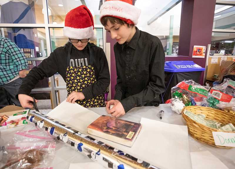 SPOKESMAN PHOTO: JONATHAN HOUSE  - Dylan, center, and Riley Guidry wrap gifts to raise money for their trips to Costa Rica.