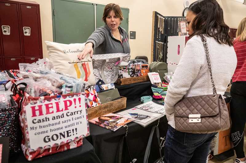 SPOKESMAN PHOTO: JONATHAN  HOUSE - Tiffany Carnathan, an independent Thirty-One Consultant, helps a customer during the Holiday Market at Inza R. Wood Middle School.