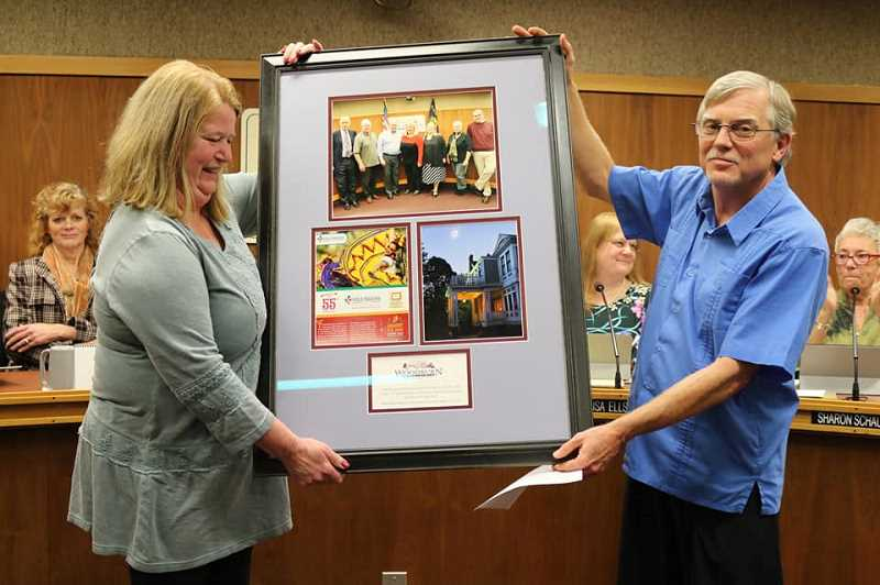 COURTESY PHOTO: CITY OF WOODBURN - Incoming Mayor Eric Swenson presents a framed photo collage to outgoing Mayor Kathy Figley Dec. 10 as a parting gift, thanking her for her many years of service to the city.