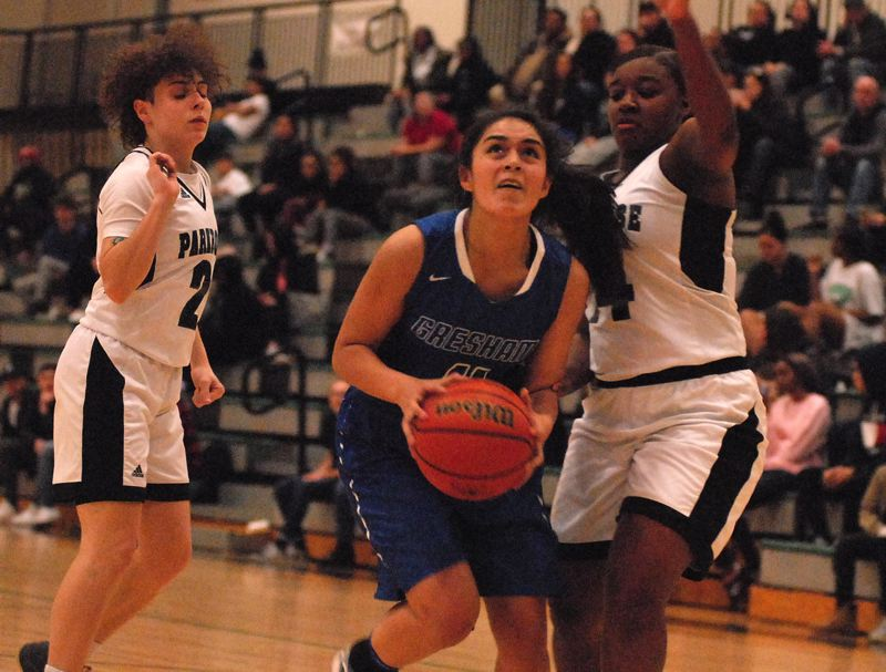 OUTLOOK PHOTO: DAVID BALL - Greshams Steff Arrango finds her way to the basket between a pair of Parkrose defenders during the Gophers 44-41 road loss Tuesday night.