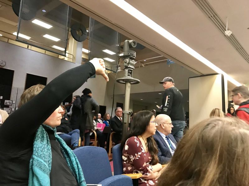 TRIBUNE PHOTO: SHASTA KEARNS MOORE - An audience member expresses her displeasure at the Portland Public Schools board for voting down an amendment to delay a vote on a police agreement while several people walk out of the meeting.