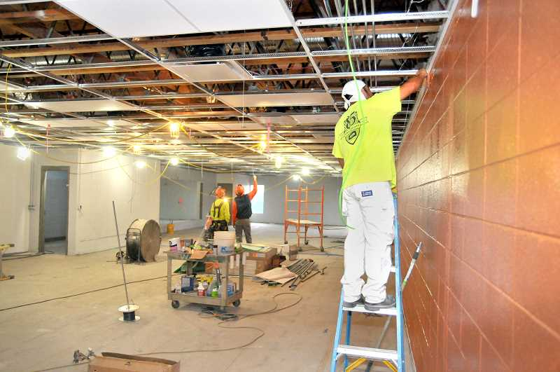 GARY ALLEN - Workers put the finishing touches on the expanded weight room, including a coat of paint on the walls.