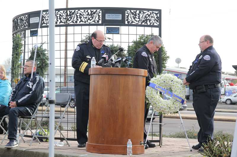 PHIL HAWKINS - Officers Jorge Gaspar (center) and Craig Halupowski place a wreath on the memorial in memory of Capt. Tom Tennant, who died exactly 10 years ago in the Woodburn West Coast Bank bombing. Chief Jim Ferraris looks on.