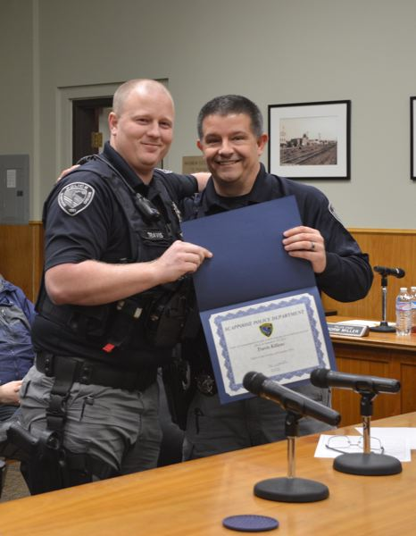SPOTLIGHT PHOTO: COURTNEY VAUGHN - Scappoose Police Officer Travis Killens (left) is presented with an award for going above and beyond while on duty by Police Chief Norm Miller.