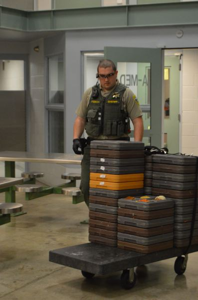 SPOTLIGHT FILE PHOTO - A jail deputy delivers meals to inmates at the Columbia County Jail in St. Helens. Columbia County is named in a federal lawsuit alleging the county jail violated federal laws and the civil rights of an inmate with mental illness.
