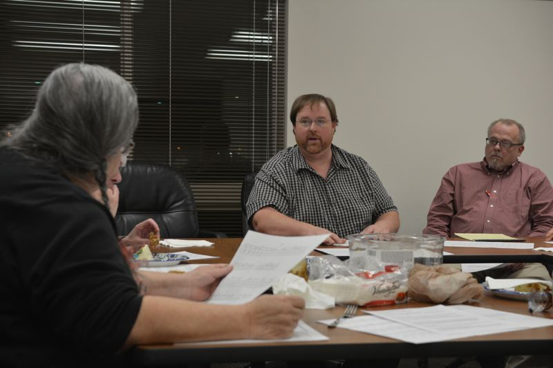 SPOTLIGHT PHOTO: COURTNEY VAUGHN - Todd Wood presents route cut options to transit advisory committee members Wednesday, Dec. 12 as committee chair Sharon Evinger (left) listens and chimes in. To Wood's right, John Dreeszen listens in.