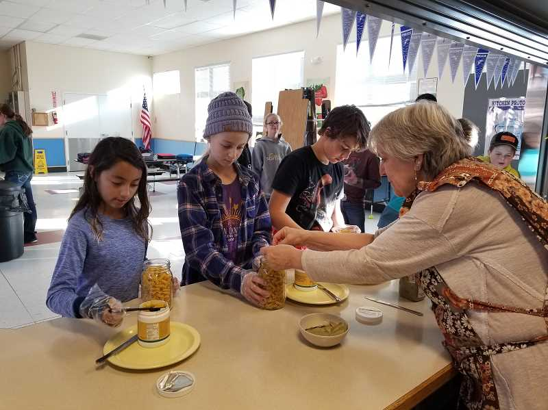 PHOTO COURTESY OF KATHY EBY  - Powell Butte Community Charter School sixth-graders create Grandma's Chicken Soup in a Jar, which will be for sale at the Christmas Bazaar Thursday, Dec. 20.