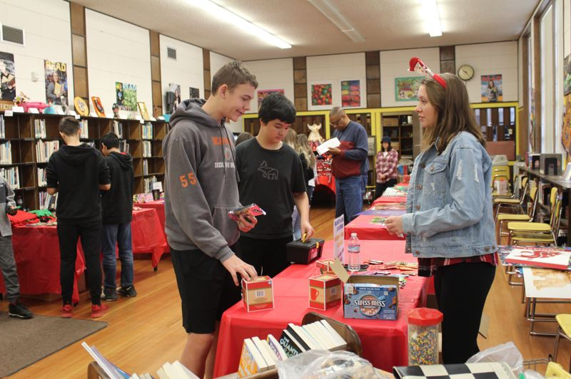 SPOTLIGHT PHOTO: NICOLE THILL-PACHECO - Pictured here eighth-graders Griffin Elliott and Sean Hall, left and center, shop for gifts at the annual Scappoose Middle School Feather Bazaar while volunteer Jenna Ramey supervises and answers questions about the cost of the items.