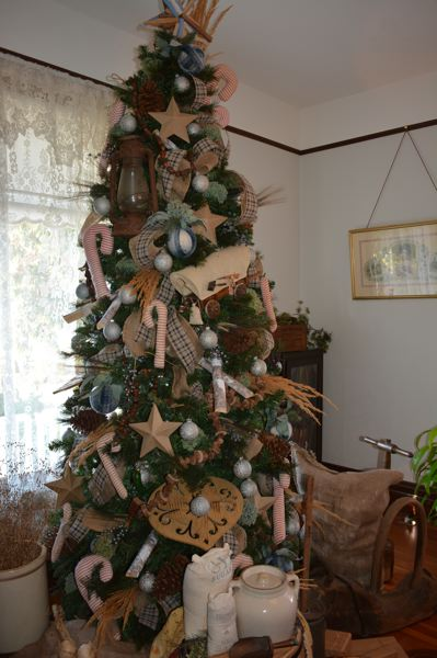 SPOTLIGHT PHOTO: COURTNEY VAUGHN - One of several trees in the Watts House features an Oregon Trail theme. Each room features a different color scheme and theme for the holidays.