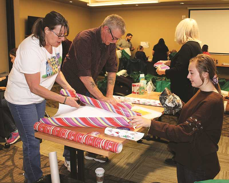 HOLLY SCHOLZ/CENTRAL OREGONIAN   - Cathy Cottle, left, who works at Regency, and her husband, Dean Cottle, wrap gifts for local senior citizens along with Bailey Everest, whose mother also works at Regency.