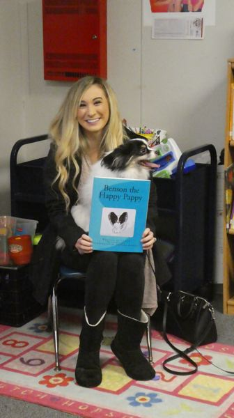 PHOTO COURTESY OF WENDY WELLS AND THE COLUMBIA CITY COMMUNITY LIBRARY - Author Caitie Dunnington poses with her dog, Benson, during a book reading at the Columbia City Community Library on Saturday, Dec. 1.