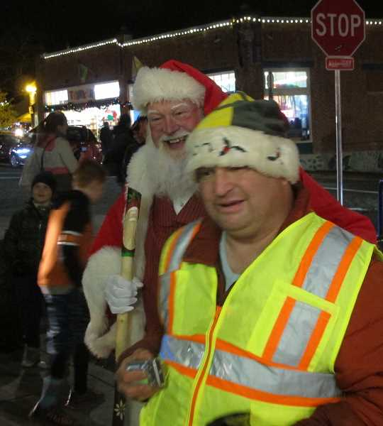 An ambulatory Santa made his way along Capitol Highway before the tree lighting.  Ernie Hunter, who walked over from Hillsdale to get a picture taken with  Santa, says he never misses the Multnomah Village tree lighting.