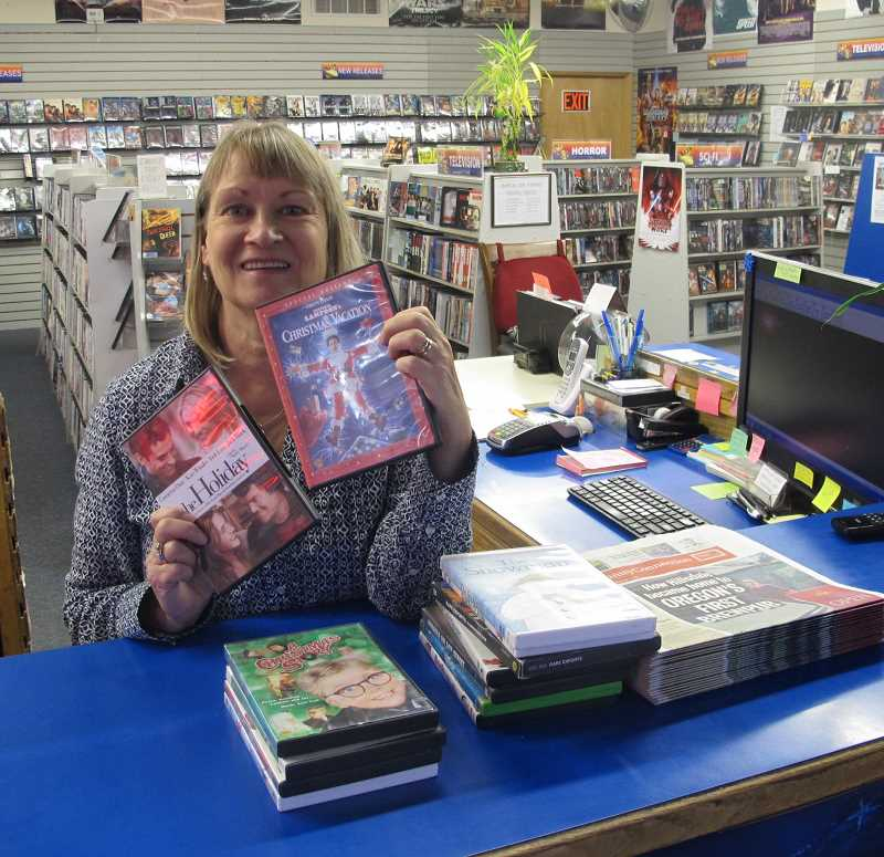 PHOTO BY BILL GALLAGHER - Impulse Video owner Karen Schoff poses at the counter of her Hillsdale store and shows off a couple of her favotie holiday movies.