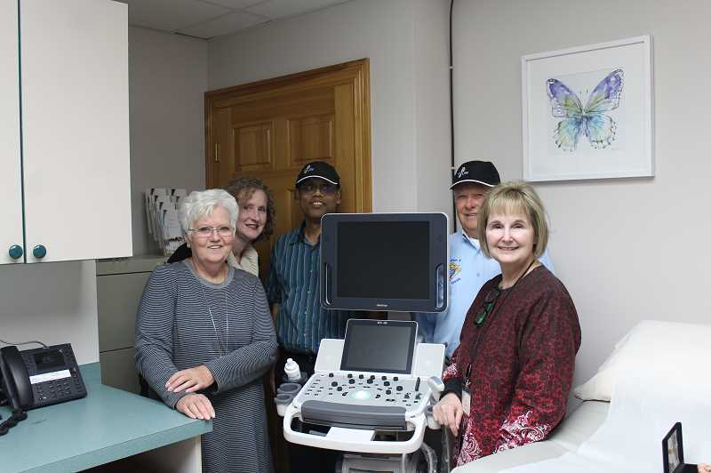 PAMPLIN PHOTO: KRISTEN WOHLERS - Some Pregnancy Care Centers staff members, including Executive Director Linda Fender (left) pose with the Knights of Columbus and the new ultrasound machine at the open house on Dec. 4.