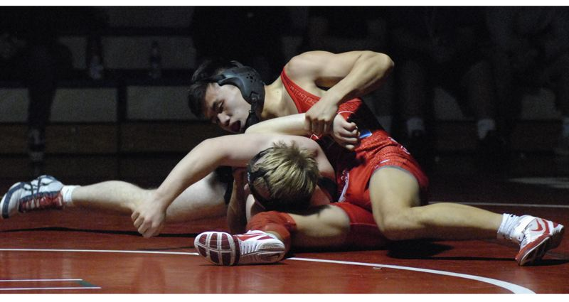 OUTLOOK PHOTO: DAVID BALL - Centennials Phillip Kue works to turn his opponent on his way to a third-round pin at 138 pounds.