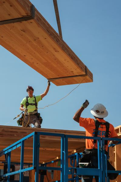COURTESY: SHAWN RECORDS - Workers lower a cross-laminated timber panel as work progresses on a new pavilion, part of an expansion and renovation at the headquarters of the Oregon chapter of the The Nature Conservancy in Portland.