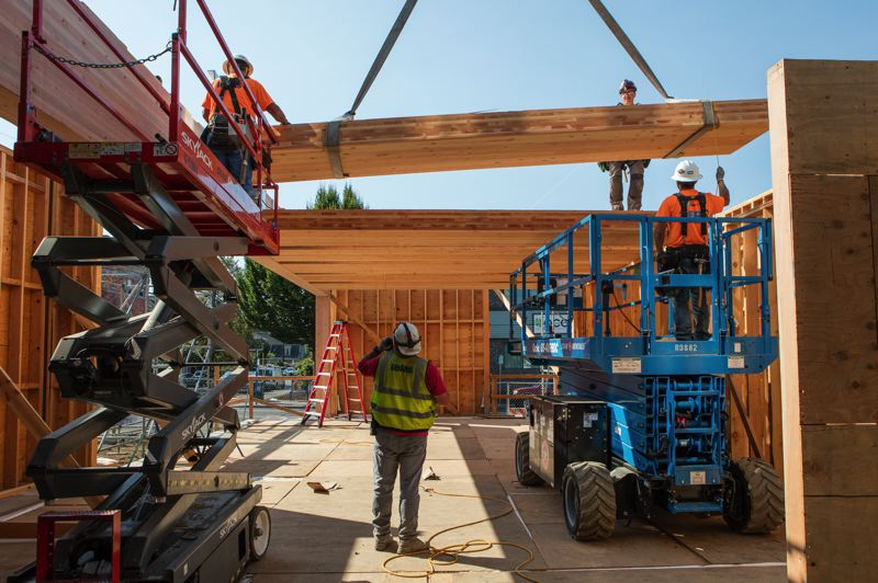COURTESY: SHAWN RECORDS  - Workers lower panels for a new pavilion being added to the headquarters of The Nature Conservancy's Oregon chapter. The project, along with a renovation of the main building, is slated for completion at the beginning of next year.