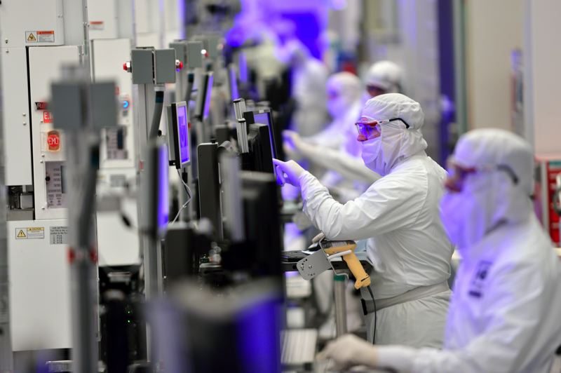 COURTESY: INTEL - Intel workers in the D1X plant in Hillsboro, Oregon, making chips. The company announced plans to expand its fabs in Oregon, Ireland and Israel as it goes beyond the PC market into phones, cars and cloud servers.