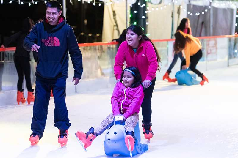 STAFF PHOTO: CHRISTOPHER OERTELL - Grownups and children enjoy a skate around the rink at the Winter Village skating rink at Jerry Willey Plaza in Orenco Station.