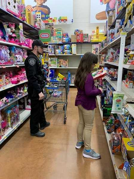 COURTESY PHOTO: MOLALLA POLICE - Molalla Police Officer Jarred Brenner helps a child pick a toy during the event.