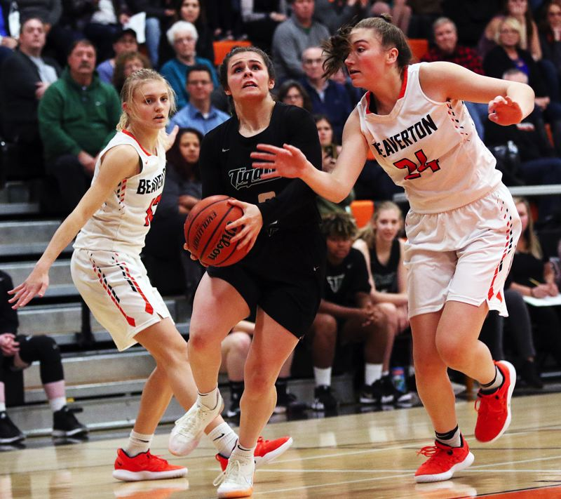 TIMES PHOTO: DAN BROOD - Tigard junior Kennedy Brown looks to drive to the basket between Beaverton's Mary Kay Naro (left) and Alexa Borter during Friday's game.