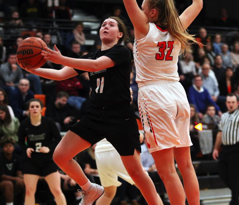 TIMES PHOTO: DAN BROOD - Tigard senior Paige LaFountain (left) goes to the basket against Beaverton junior Sydney Erikstrup during Friday's game.