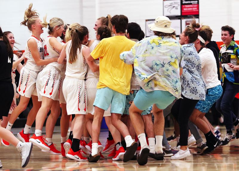 TIMES PHOTO: DAN BROOD - Beaverton students storm the court to celebrate with the team following Friday's 41-40 win over Tigard.