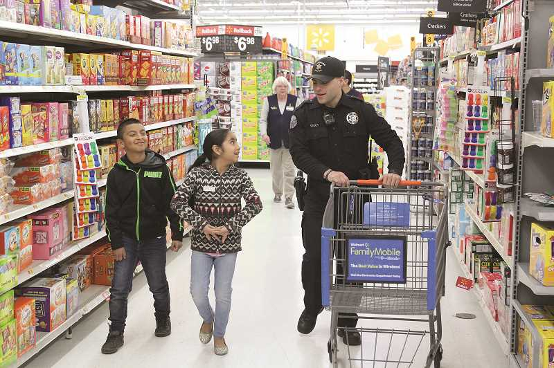 PHIL HAWKINS - Woodburn Police Department Officer Jacob Stout walks with a couple Woodburn students through the aisles of Walmart during the annual shop with a cop event held Thursday and Friday last week.