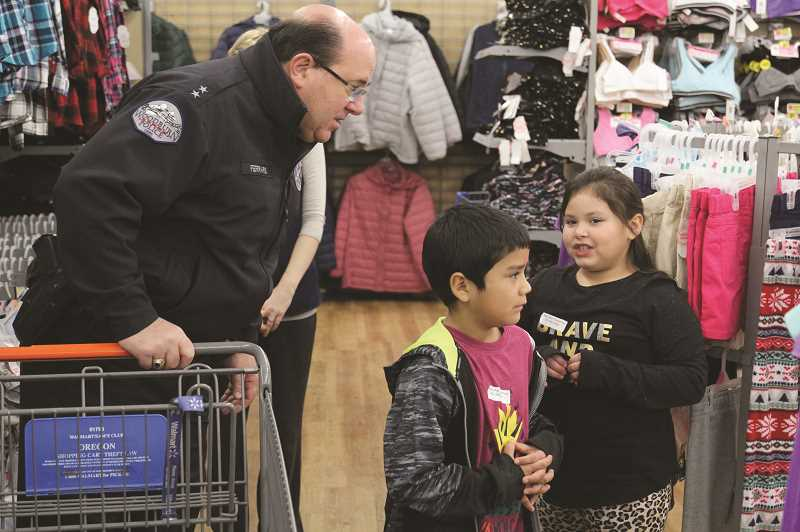PHIL HAWKINS - WPD Chief Jim Ferraris consults with a youth interested in buying clothes.