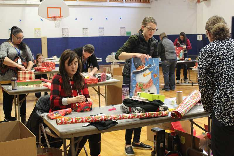 KRISTEN WOHLERS - Ninety-One school parents gather like elves on Monday, Dec. 10 to wrap presents for 39 of the school's families that could use extra help this season. The families will also receive a food box, books, socks and underwear.