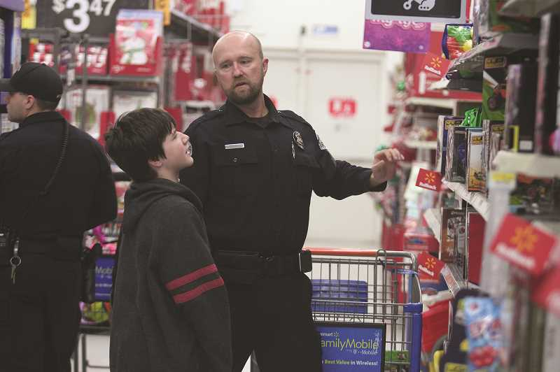 PHIL HAWKINS - WPD Officer Andy Shadrin helps his assigned student on selecting a gift item from the shelf.