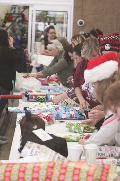 PHIL HAWKINS - METCOM employees lined up to wrap the gifts selected by the children.