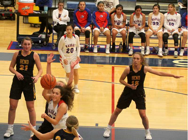 STEELE HAAUGEN - Jayden Davis drives the ball past a Bend defender and makes a pass to a teammate. Davis had 8 points, seven rebounds and two assists, but the Lady Buffs lost 63-50