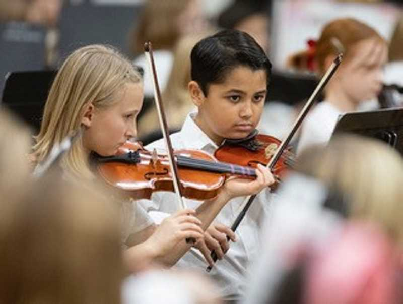 SPOKESMAN PHOTO: JONATHAN HOUSE  - Audrey Arndt, left, and Alex Chandra perform during the orchestra concert.